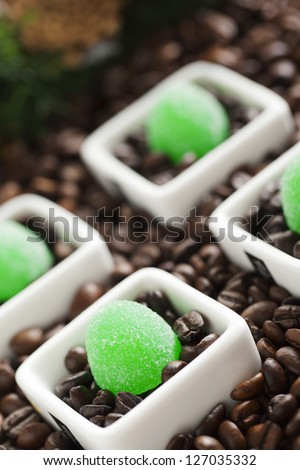 Coffee beans with jelly candies on a dish - stock photo