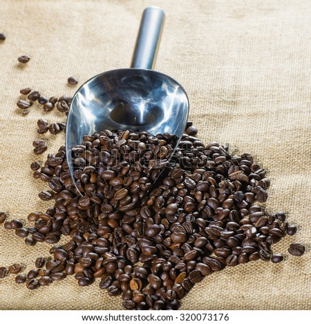 Coffee beans with measuring scoop on burlap - stock photo