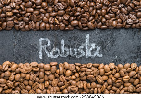 Coffee beans with Robusta hand writing on black wooden background with blank space. - stock photo