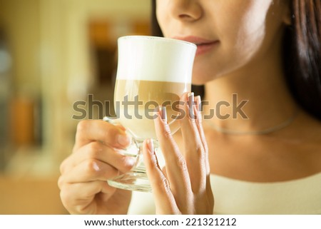 Coffee. Beautiful Girl Drinking Tea or Coffee in Cafe. Beauty Model Woman with the Cup of Hot Beverage. Warm Colors Toned - stock photo
