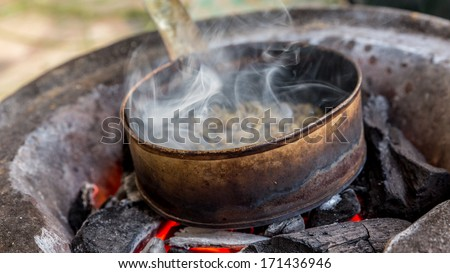Coffee being roasted on a pan over charcoal in the Ethiopian traditional way - stock photo