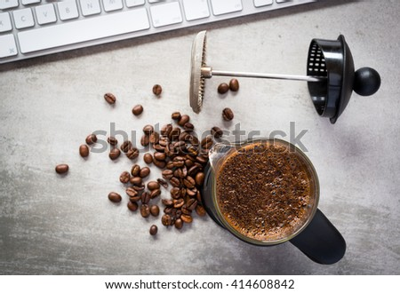 Coffee break at work. A french press coffee can and a computer keyboard. Coffee beans on concrete table. - stock photo