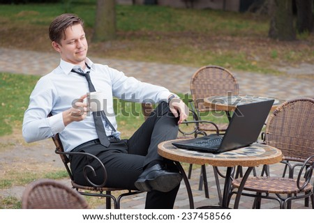 Coffee break. Attractive young caucasian businessman in formal wear working on laptop while relaxing in sidewalk cafe holding cup of coffee - stock photo