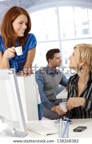 Coffee break in office, businesswomen chatting, holding coffee cup, smiling. - stock photo