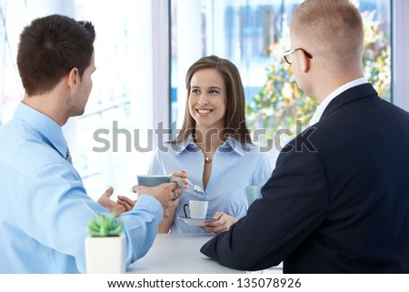 Coffee break in office, coworkers enjoying free time and conversation, smiling. - stock photo