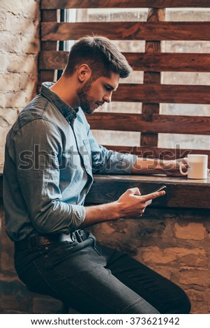 Coffee break. Side view of handsome thoughtful young man holding smart phone and looking at it while sitting near window in loft interior with coffee cup in his hand - stock photo