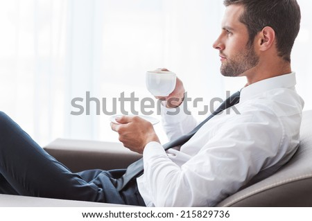 Coffee break. Side view of thoughtful young businesswoman in suit drinking coffee and looking away while sitting at the chair - stock photo