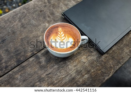 Coffee Break Symbol, Latte art coffee cup with notebooks computer on wood desk view from above - stock photo