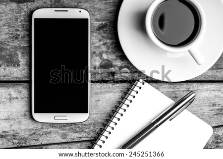Coffee break top view black and white image. Smart phone with notebook, fountain pen and cup of coffee. - stock photo