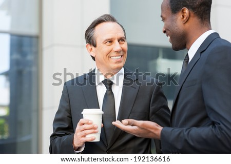 Coffee break. Two cheerful business men talking outdoors while one of them holding coffee cup  - stock photo