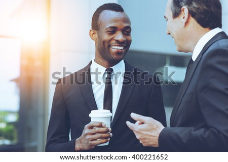 Coffee break. Two cheerful business men talking while one of them holding coffee cup - stock photo