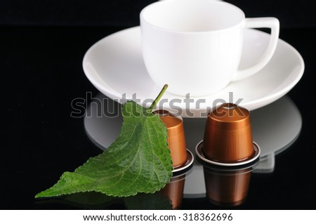 coffee capsules and green leaf isolated on black background - stock photo