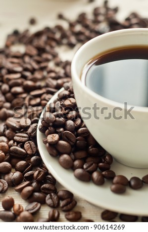 Coffee close up surrounded by coffee beans - stock photo