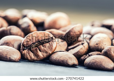 Coffee. Coffee beans. Roasted coffee beans spilled freely on a table.Coffee time