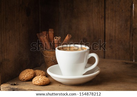 Coffee cup, Amaretti and Cinnamon sticks on wooden background