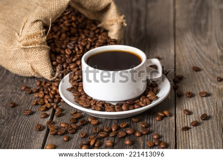 Coffee cup and bag with coffee beans on wooden table.