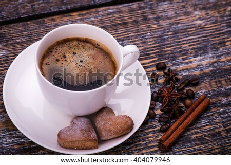 Coffee cup and beans, cookies on a wooden table. Dark background. - stock photo