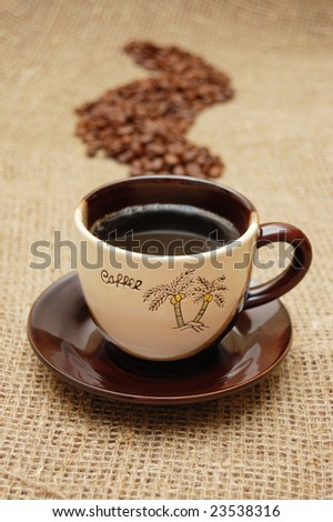 Coffee cup and beans in shape of steam on hessian canvas