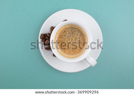 Coffee cup and beans on a blue  background - stock photo