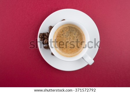 Coffee cup and beans on a red background - stock photo