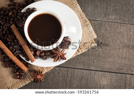 Coffee cup and beans on a rustic background. Coffee Espresso and a piece of cake with a curl. Cup of Coffee and coffee beans on table.