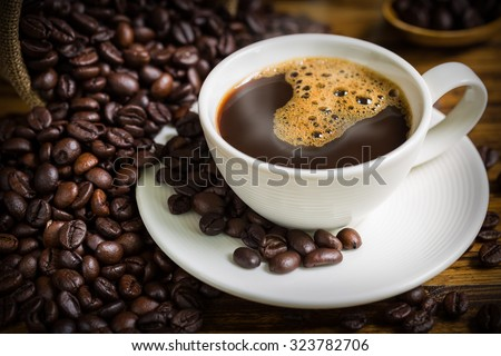 Coffee Cup and Beans on Wooden Table - stock photo