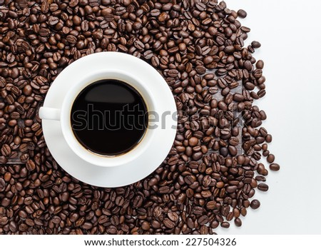 Coffee cup and beans with white area for copy space. - stock photo