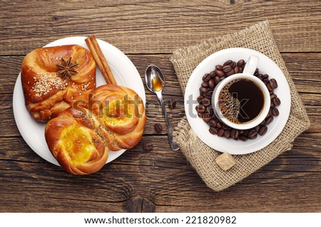 Coffee cup and buns on vintage wooden table. Top view - stock photo