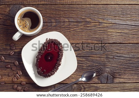 Coffee cup and cake with cherry jelly on dark wooden table, top view  - stock photo