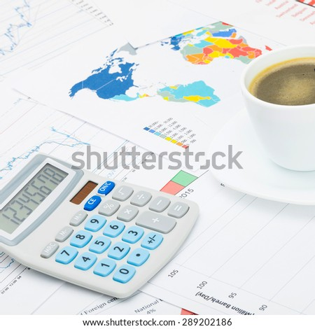 Coffee cup and calculator over financial charts - close up - stock photo