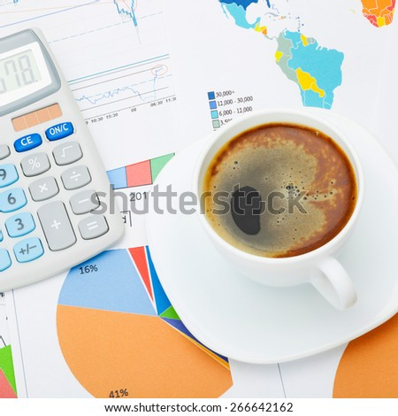 Coffee cup and calculator over financial charts - studio shot - stock photo