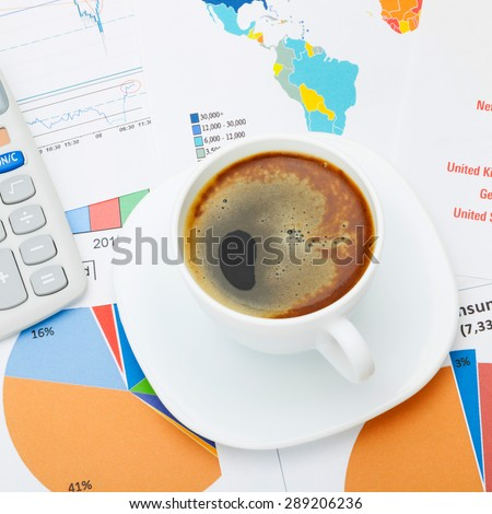 Coffee cup and calculator over financial documents - close up shot - stock photo