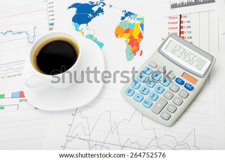 Coffee cup and calculator over world map and stock charts - stock photo