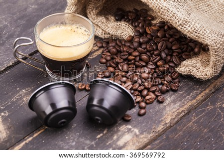Coffee cup and capsules on a rustic wooden table - stock photo
