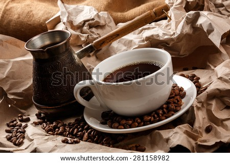 Coffee cup and cezve for turkish coffee on crumpled paper surface