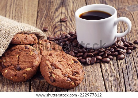 Coffee cup and chocolate cookies with nuts on old wooden table - stock photo