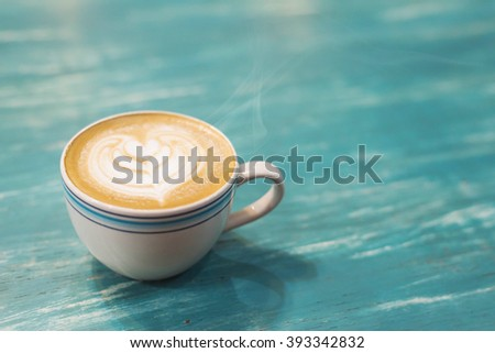 coffee cup and coffee beans.Coffee cup and coffee beans on a wooden table and sack background,Vintage color tone - stock photo