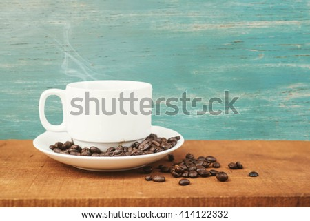 coffee cup and coffee beans.Coffee cup and coffee beans on a wooden table and sack background,Vintage color tone. - stock photo