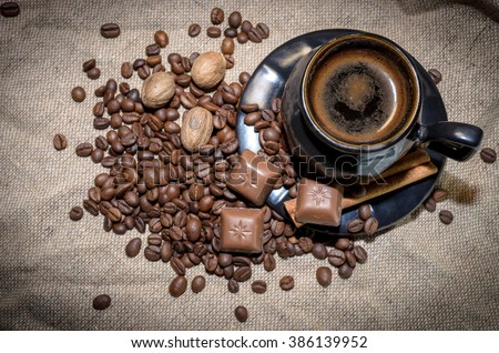 Coffee cup and coffee beans, nutmegs, chocolate  and cinnamon sticks on a sack background - stock photo