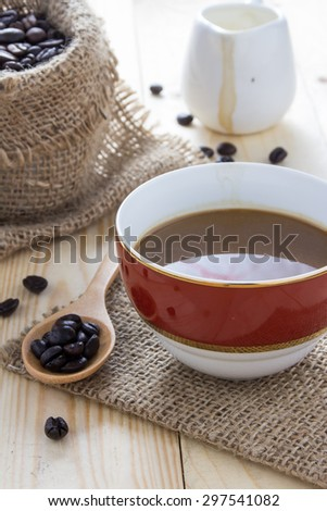 Coffee cup and coffee beans on a wooden table. - stock photo