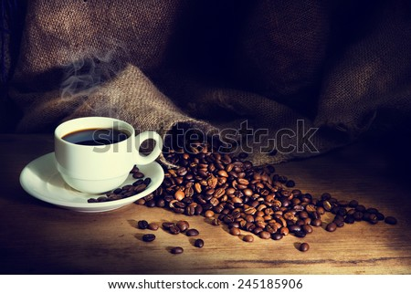Coffee cup and coffee beans on a wooden table and sack background,Vintage color tone - stock photo