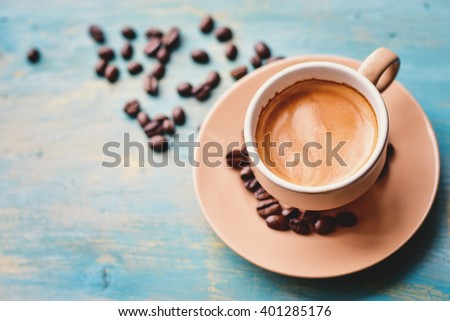 Coffee cup and coffee beans on blue background. Top view. - stock photo