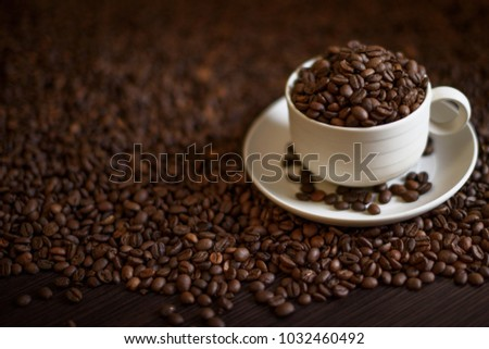 Coffee cup and coffee beans on wooden table. Coffee beans close up.