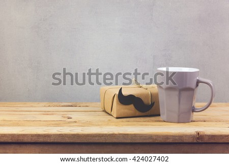 Coffee cup and gift box on wooden table. Father's day holiday concept - stock photo