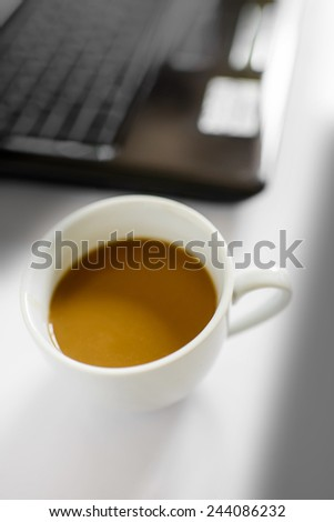 Coffee cup and laptop for business, Selective focus on coffee. - stock photo