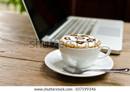 Coffee cup and laptop on the wood texture, selective focus on coffee cream.