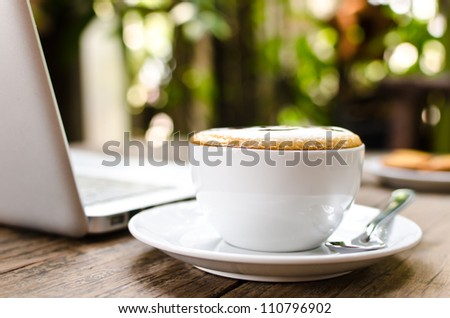 Coffee cup and laptop on the wood texture, selective focus on coffee cream. - stock photo
