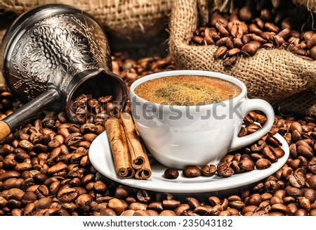 Coffee cup and metal turk on burlap background