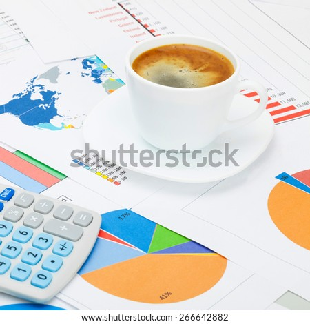 Coffee cup and neat calculator over world map and financial charts - close up shot - stock photo