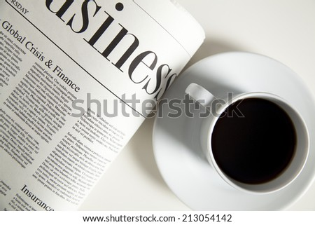 Coffee cup and newspaper, high angle view - stock photo